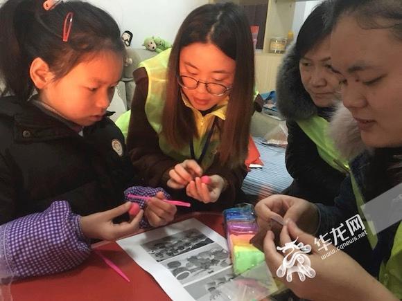 志愿者陪患有先天性耳聋的小颜欣一起做手工。实习生 邓琳弋 摄.jpg